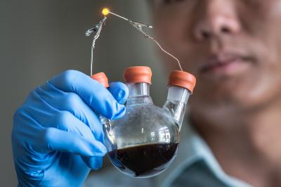 SLAC/Stanford's Yi Cui holds a lab demonstration of his group's new lithium-polysulfide flow battery contained in a simple flask. The design could serve as a model for a low-cost, long-life battery that enables solar and wind energy to become major suppliers to the electrical grid. Credit: Matt Beardsley, SLAC National Accelerator Laboratory