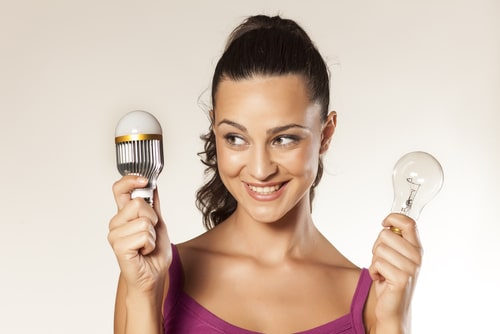 young girl holding new and old generation lights shutterstock_150541364
