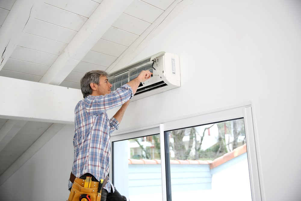 Repairman fixes AC unit shutterstock_176086514