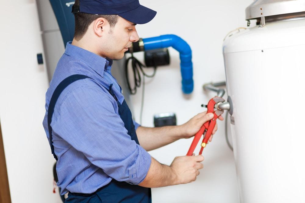 plumber repairing water heater shutterstock_147935285