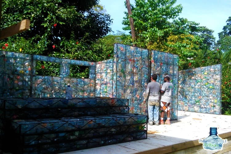 Wire frames hold bottles in wall form at Plastic Bottle Village