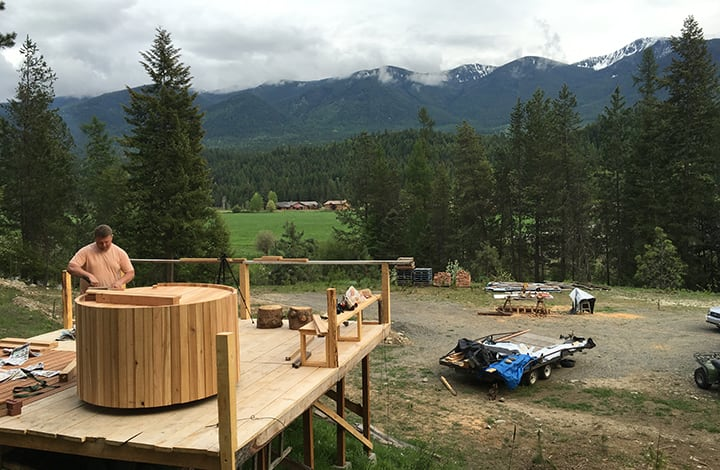 A wood-fired hot tub has been added to the off-grid cabin so the owners can relax after a hard day of homesteading.