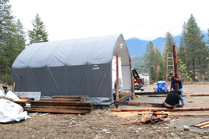 The off-grid cabin is an extension of a carport used to shelter the couple's travel trailer.