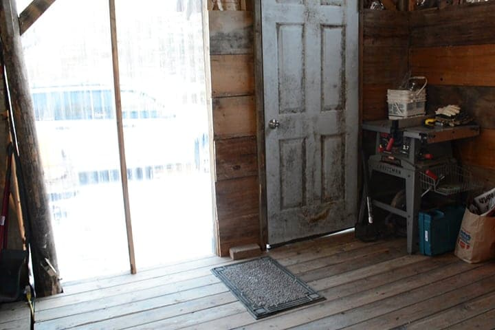 The interior of the off-grid cabin includes a wood stove, water heater, and water pump.